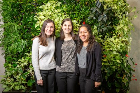 Student externs pose with host in front of a green wall