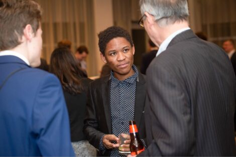 Student listens attentively as he networks with alum