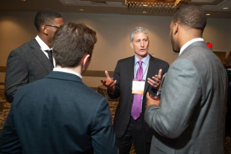 Alum JB Reilly talks to a group of young men at Networking Night