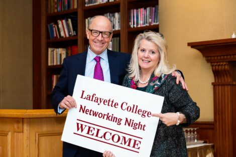 Alumni hold welcome sign for NYC Networking Night