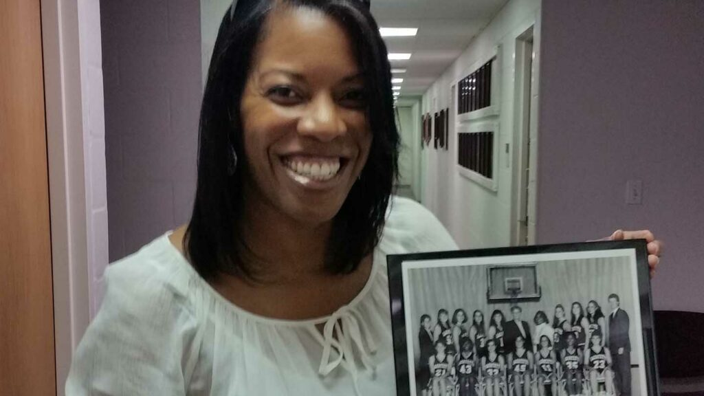 """Kareema J. Gray, Ph.D., '94 with a photo of her women's basketball teammates. """"Being a student-athlete at Lafayette taught me discipline, and how to organize and prioritize,"""" she says."""