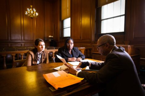 Students participating in externship sit with judge in a New York State courtroom