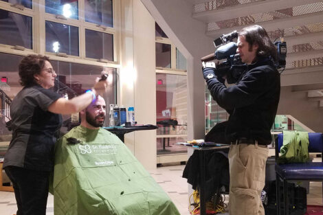 A WFMZ cameraman films a student getting his head shaved for a cancer charity event.