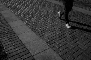Black and white image of a student's feet as they rush to class across the quad,