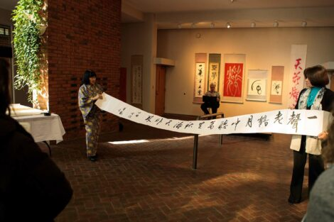 calligraphy master Shuho Kondo holds up scroll