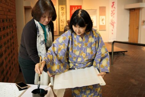 calligraphy master Shuho Kondo dips her brush in the ink