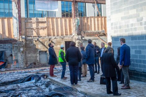 Students and local alum stand inside new construction in Easton