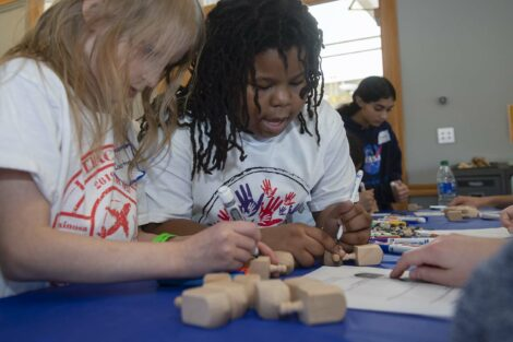 Two children work on decorating dreidels