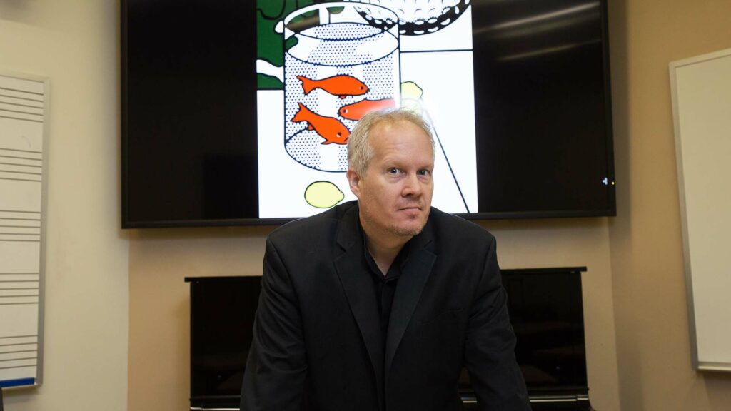 Kirk O'Riordan standing in classroom in front of piano and artwork