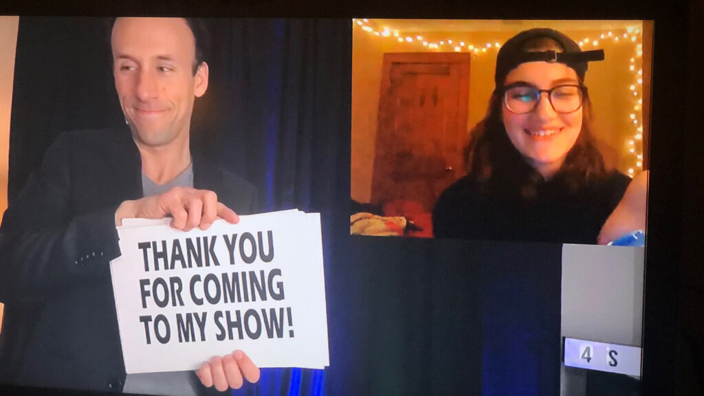 "Magician holds up a ""Thank you for coming to my show"" sign"