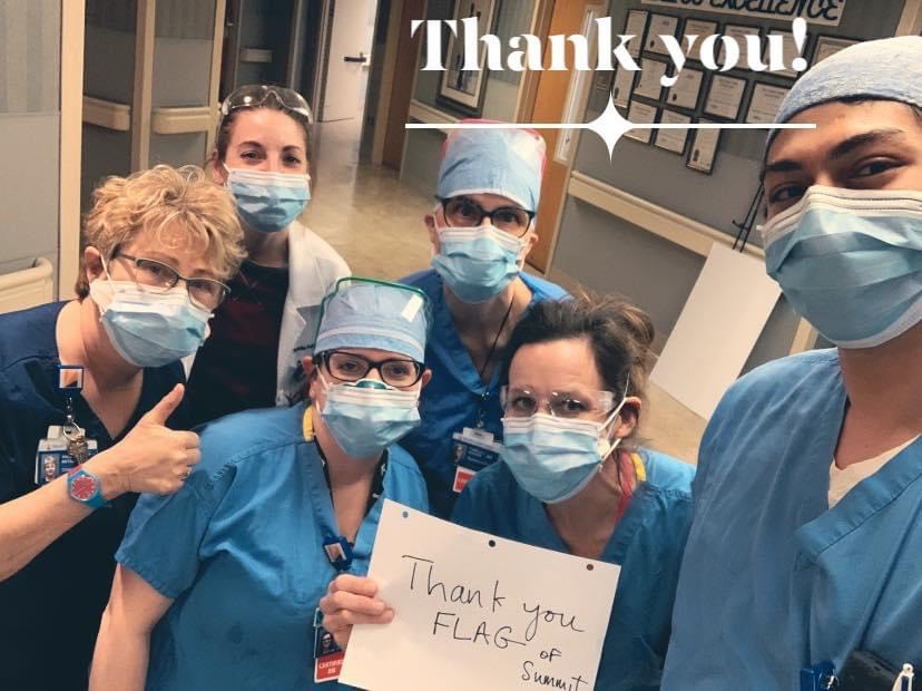 Healthcare professionals in scrubs hold up a sign thanking FLAG of Summitt.