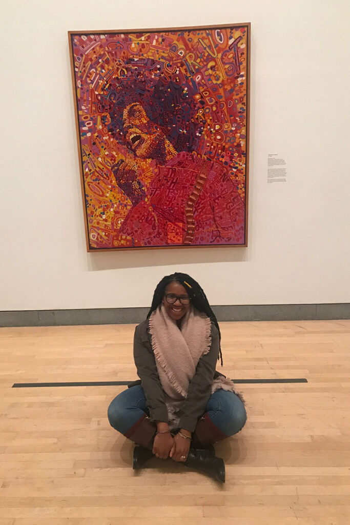 J'Nisha Little '20 sits in front of a painting