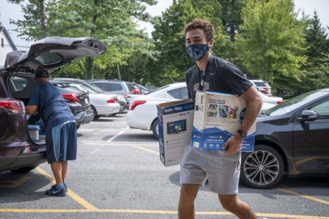 A masked student carries boxes into residence hall.