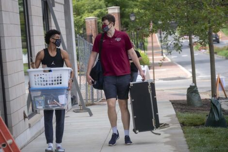 Two masked students carry belongings into residence hall.