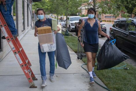 A masked student and family member carries belongings.