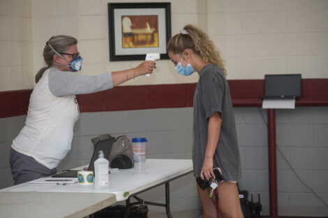A masked healthcare worker gives a masked student a temperature check.
