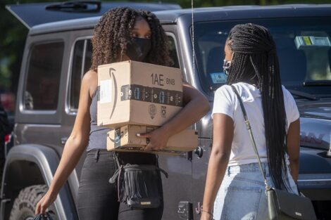 A masked student carries a box and talks to another student