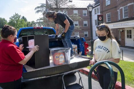 A masked student and her family unload belongings from their truck