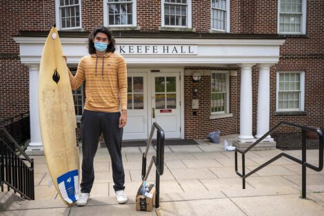 A masked student with their surfboard outside of Keefe Hall.
