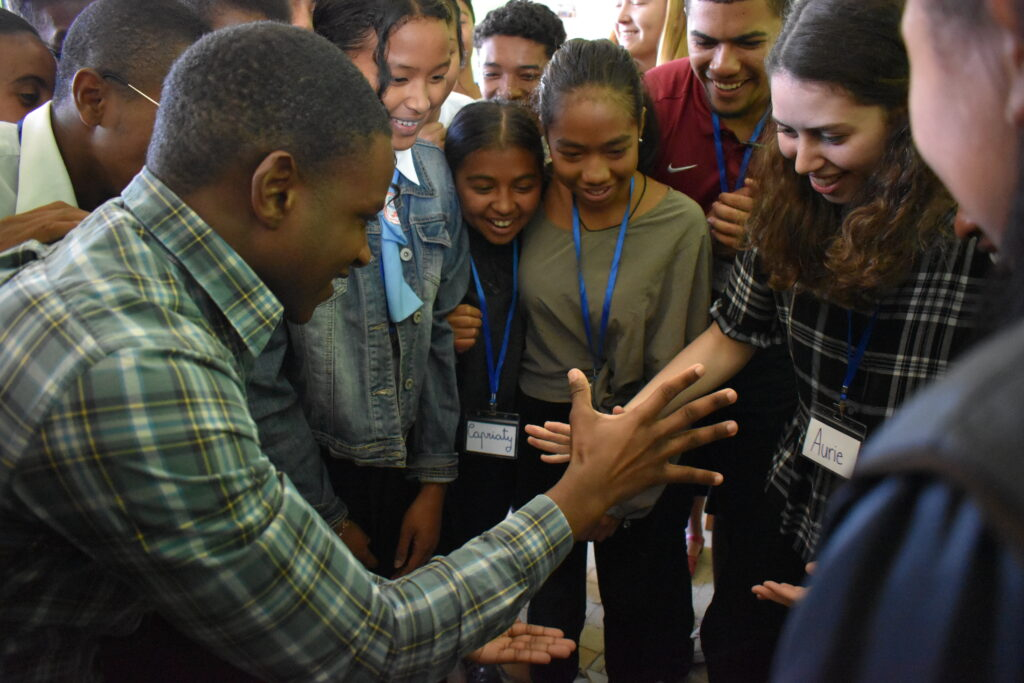 Aurie Greenberg '22, right, participates in a group exercise with a group of Malagasy students at Lycée Andohalo.