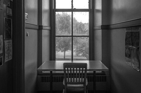 A desk and chair in front of a tall window.
