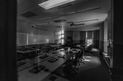 Black and white image of desks and chairs in an empty classroom of Pardee Hall.