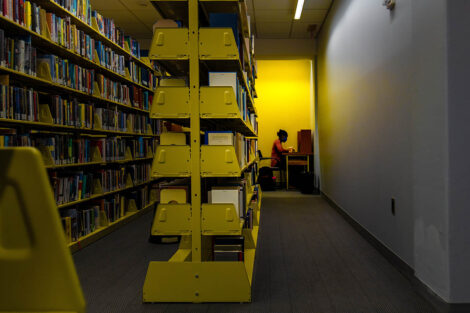 A student, in a mask, studies behind a bookshelf.