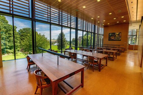 A row of empty tables in front of a window showing the Quad, inside of Skillman Library