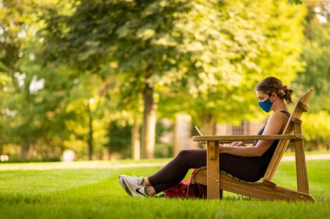 student reads in a mask on the Quad