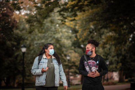 two students wearing masks walk on campus