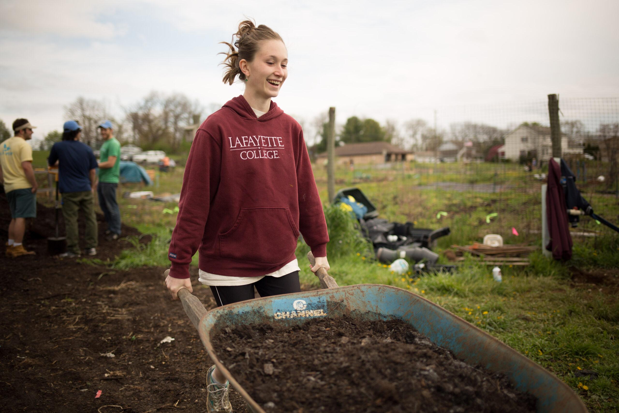 Miranda Wilcha pushing a wheelbarrow at LaFarm