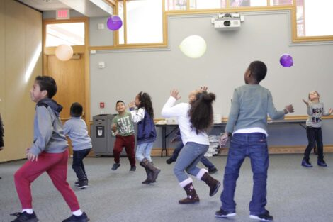 Elementary students chase balloons in activity