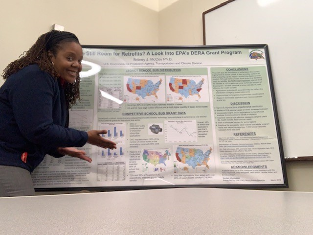 Britney McCoy '05 stands in front of a poster of research, smiling and gesturing to the poster.