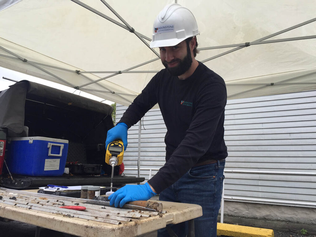 Bryan McAtee '11, wearing a construction hat, uses tools on a table.