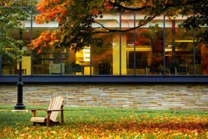 empty chair on the Quad with leaves on the ground and Skillman in background