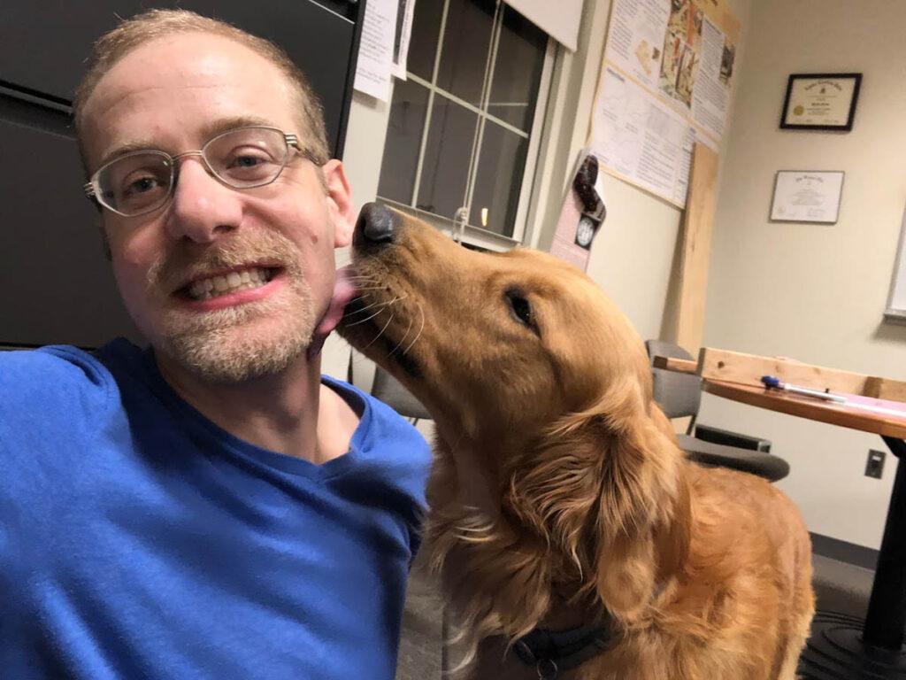 Prof. Dave Mante smiles as his golden retriever Charlie licks his cheek.