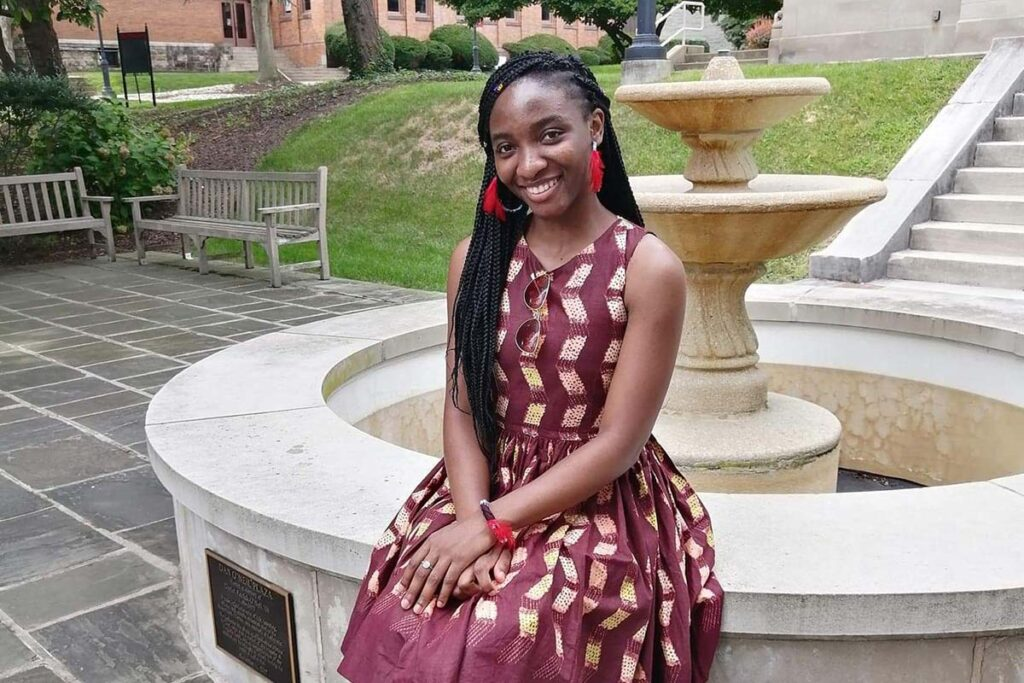 portrait of Jelissa Kamguem '23, sitting outside on the ledge of a fountain