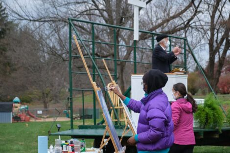 Students paint while preacher preaches