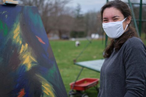 Student in mask poses with art
