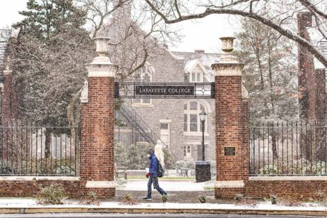 a student in a mask walks near a campus gateway as snow falls