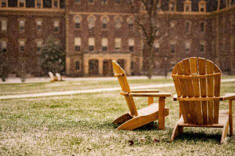 a light snow falls on Adirondack chairs on the Quad