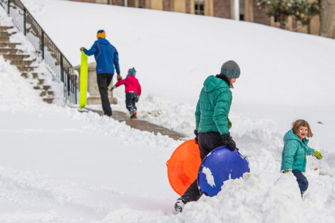 adults and children carry sleds toward the steps behind Pardee Hall