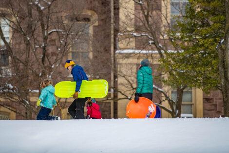 a family walks with sleds through the snow near Pardee Hall