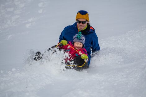 a father and child sled down a hill in the snow