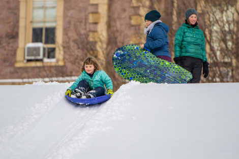 a young child sleds down a hill in the snow near Pardee Hall