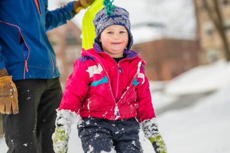 a young child is bundled up in the snow on campus
