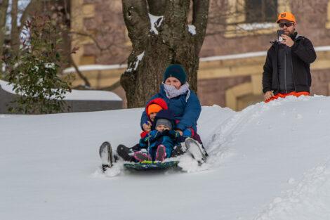 a family sleds down a snowy hill near Pardee Hall