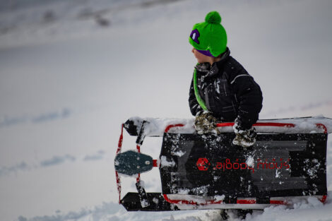a young child carries a sled on campus in the snow