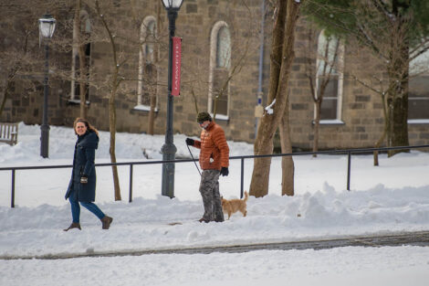 Two people walk their dog through a snow-covered campus