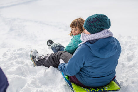 an adult and child sit on a sled in the snow on campus